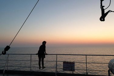 Girl looking out over Caspian Sea at sunset